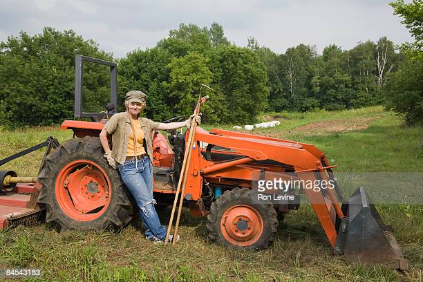Worker standing by a tractor at an organic farm