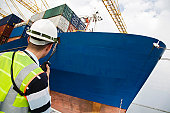 Worker Standing by Cargo Ship