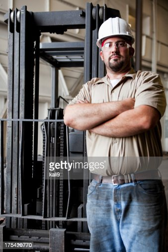 Worker standing in front of forklift
