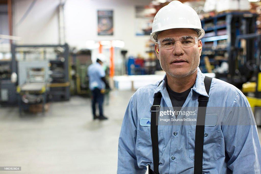 Worker standing in metal plant : Stock Photo