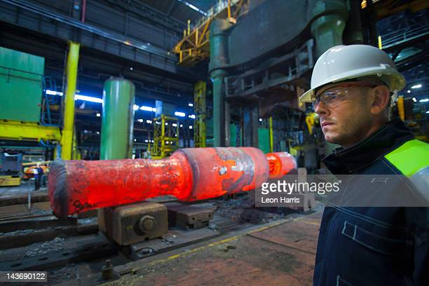 Worker standing in steel forge