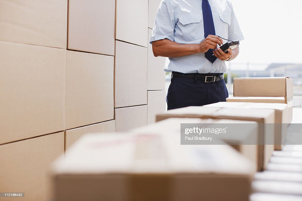 Worker standing near boxes on conveyor belt : Stock Photo