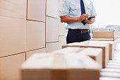 Worker standing near boxes on conveyor belt