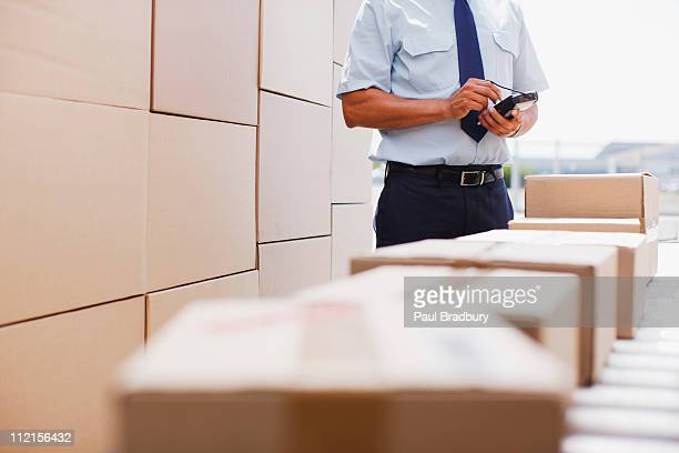 Worker standing near boxes on conveyor belt