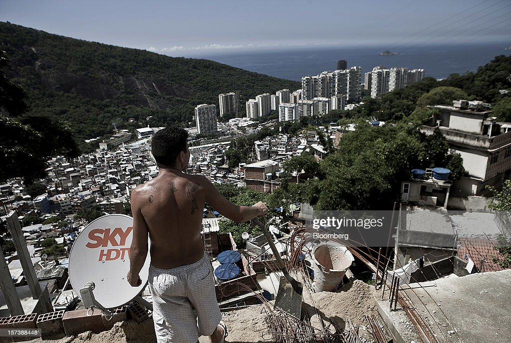 A worker standing next to a SKY HDTV satellite dish takes a break from building a water tank on the rooftop of a house in the Rocinha slum of Rio de Janeiro, Brazil, on Wednesday, Nov. 28, 2012. About 56 percent of the 12 million people who live in slums like Rocinha were considered middle class in 2011, up from 29 percent in 2001, according to a study this year by Instituto Data Popular, a Sao Paulo-based research group. Photographer: Dado Galdieri/Bloomberg via Getty Images