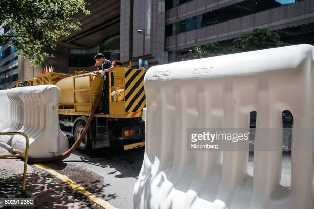 A worker standing on a water tanker fills barricades near the Hong Kong Convention and Exhibition Center ahead of Chinese President Xi Jinping's...