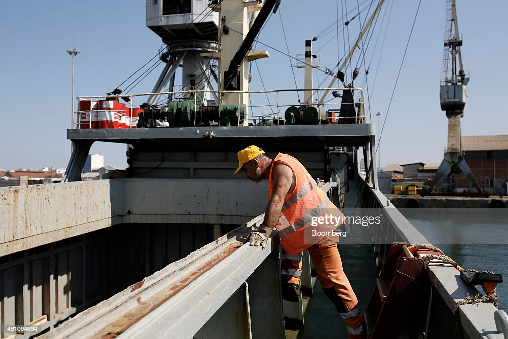 A worker stands aboard a cargo ship as sheets of metal are loaded at Thessaloniki port operated by Thessaloniki Port Authority SA in Thessaloniki...