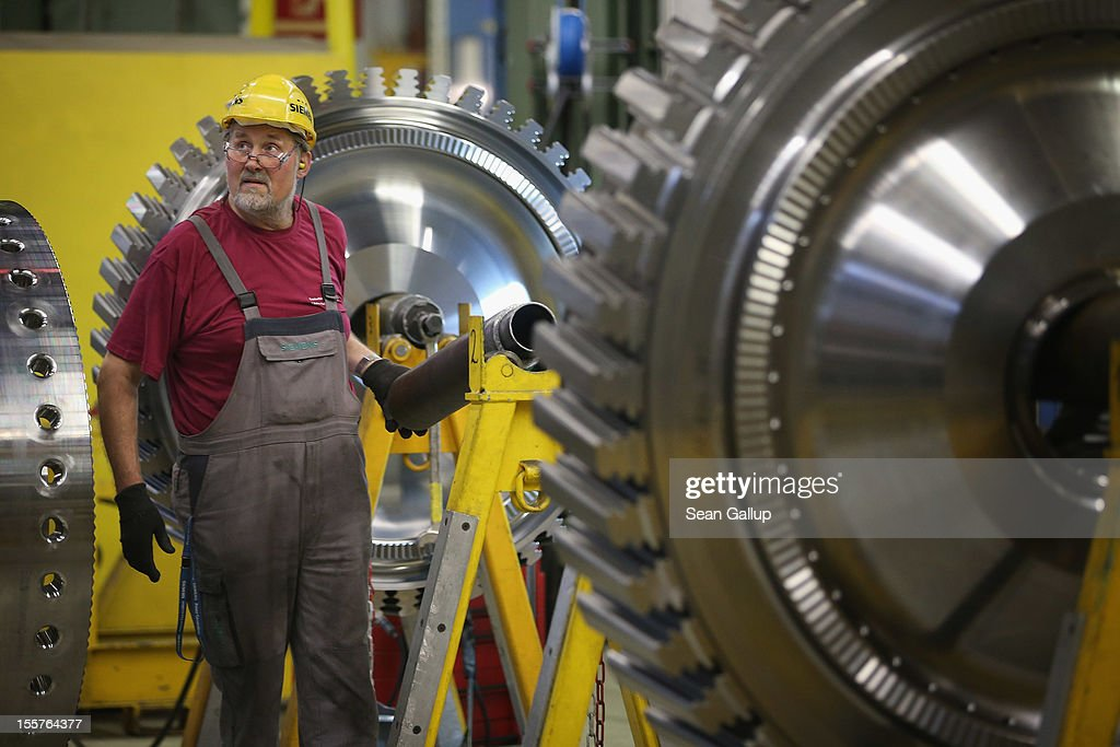 A worker stands among discs of a gas turbine at the Siemens gas turbine plant on November 11 2012 in Berlin Germany Earlier in the Siemens announced...
