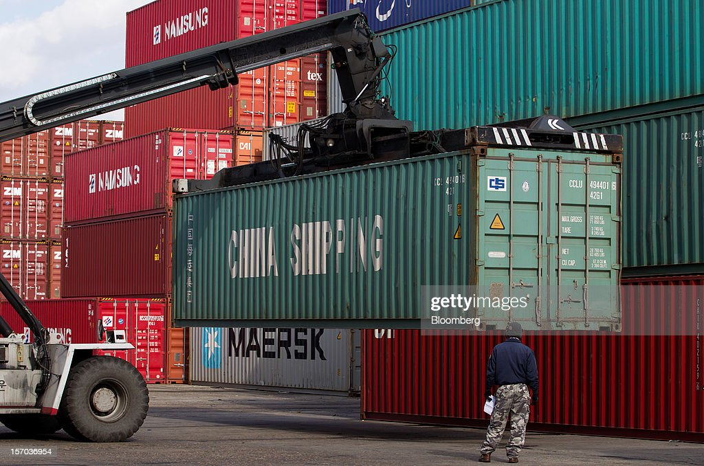 A worker stands as a straddle carrier moves a container at the Uiwang Inland Container Depot (ICD) in Uiwang, South Korea, on Monday, Nov. 26, 2012. South Korea's current-account surplus narrowed to a two-month low after imports of machinery and equipment increased. Photographer: SeongJoon Cho/Bloomberg via Getty Images