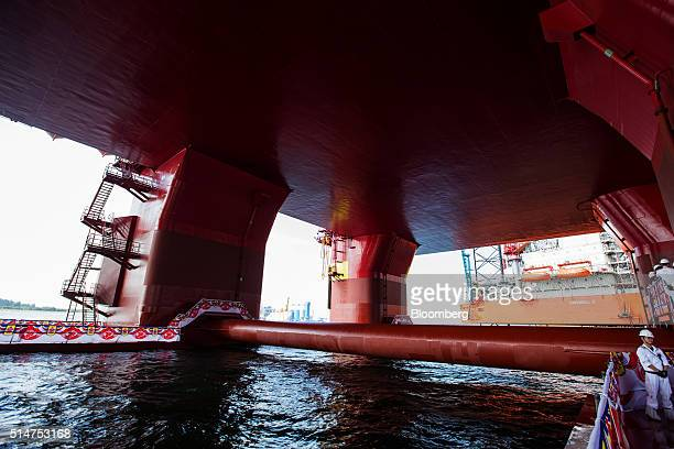 A worker stands as a water pipe runs under the Floatel Triumph a semisubmersible accommodation rig operated by Floatel International Ltd and...