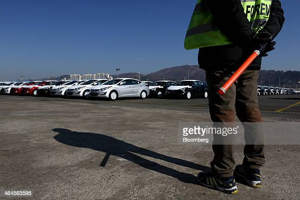 A worker stands as Hyundai Motor Co vehicles bound for export await shipment at a port near the company's plant in Ulsan South Korea on Thursday Jan...