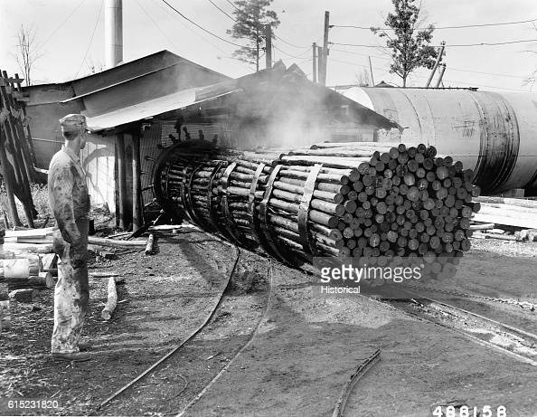 A worker stands aside as treated logs are dragged out of a creosote oven at the Summitt Post Company Shawnnee National Forest Winona Missouri USA |...