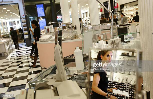 A worker stands behind a counter at the new Bloomingdale's location in the Soho neighborhood April 21 2004 in New York City The six level store which...