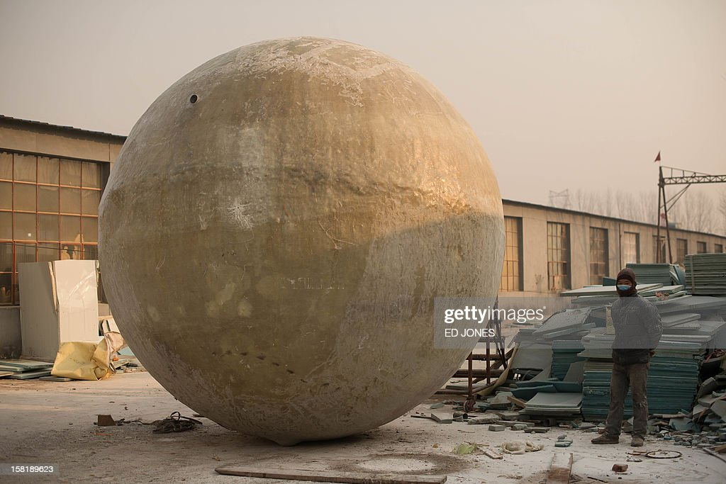 A worker stands beside a survival pod dubbed 'Noah's Arc' by its creator, farmer Liu Qiyuan, in a yard at his home in the village of Qiantun, Hebei province, south of Beijing on December 11, 2012. Inspired by the apocalyptic hollywood movie '2012' and the 2004 Asian tsunami, Liu hopes that his creations consisting of a fibreglass shell around a steel frame will be adopted by government departments and international organisations for use in the event of tsunamis and earthquakes. Liu has built seven pods which are able to float on water, some of which have their own propulsion. The airtight spheres with varying interiors contain oxygen tanks and seatbelts with space for around 14 people, and are designed to remain upright when in water. AFP PHOTO / Ed Jones