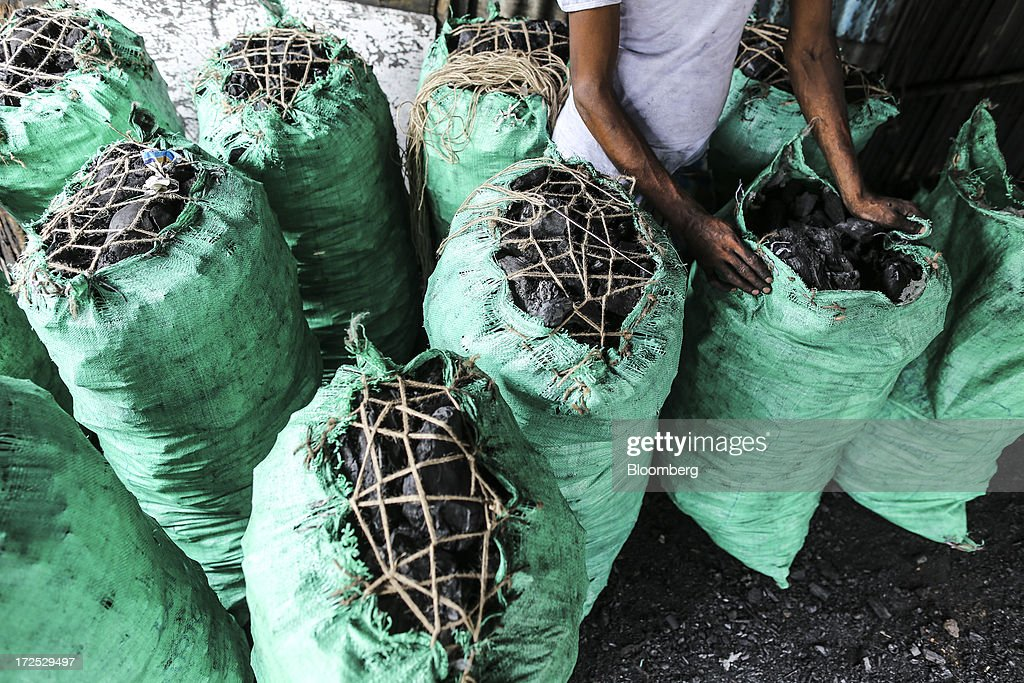 A worker stands beside bags of coal at a coal wholesale market in Mumbai, India, on Tuesday, July 2, 2013. India, the worlds third-largest coal consumer, imported 43 percent more of the fuel than a year ago on increased demand from power stations and steelmakers, according to shipping data, and is set to eclipse China as the top importer of power station coal by 2014. Photographer: Dhiraj Singh/Bloomberg via Getty Images
