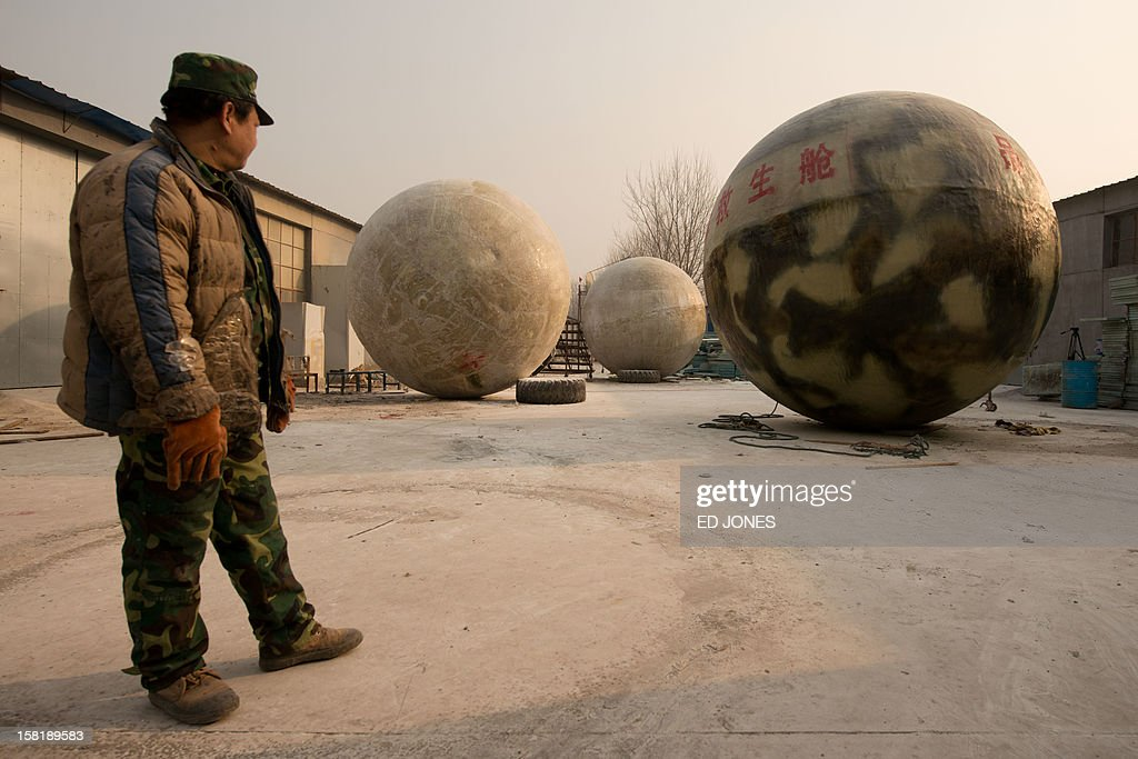 A worker stands beside survival pods dubbed 'Noah's Arc' by their creator, farmer Liu Qiyuan, in a yard at his home in the village of Qiantun, Hebei province, south of Beijing on December 11, 2012. Inspired by the apocalyptic Hollywood movie '2012' and the 2004 Asian tsunami, Liu hopes that his creations consisting of a fibreglass shell around a steel frame will be adopted by government departments and international organisations for use in the event of tsunamis and earthquakes. Liu has built seven pods which are able to float on water, some of which have their own propulsion. The airtight spheres with varying interiors contain oxygen tanks and seatbelts with space for around 14 people, and are designed to remain upright when in water. AFP PHOTO / Ed Jones