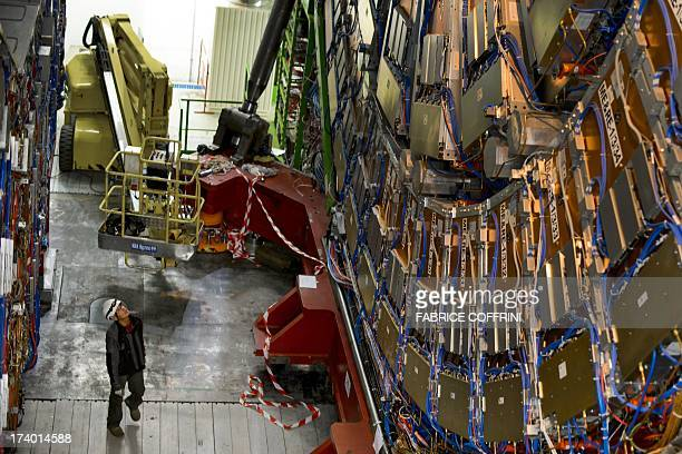 A worker stands by the CERN's Compact Muon Solenoid a generalpurpose detector at the Large Hadron Collider during maintenance works on July 19 2013...
