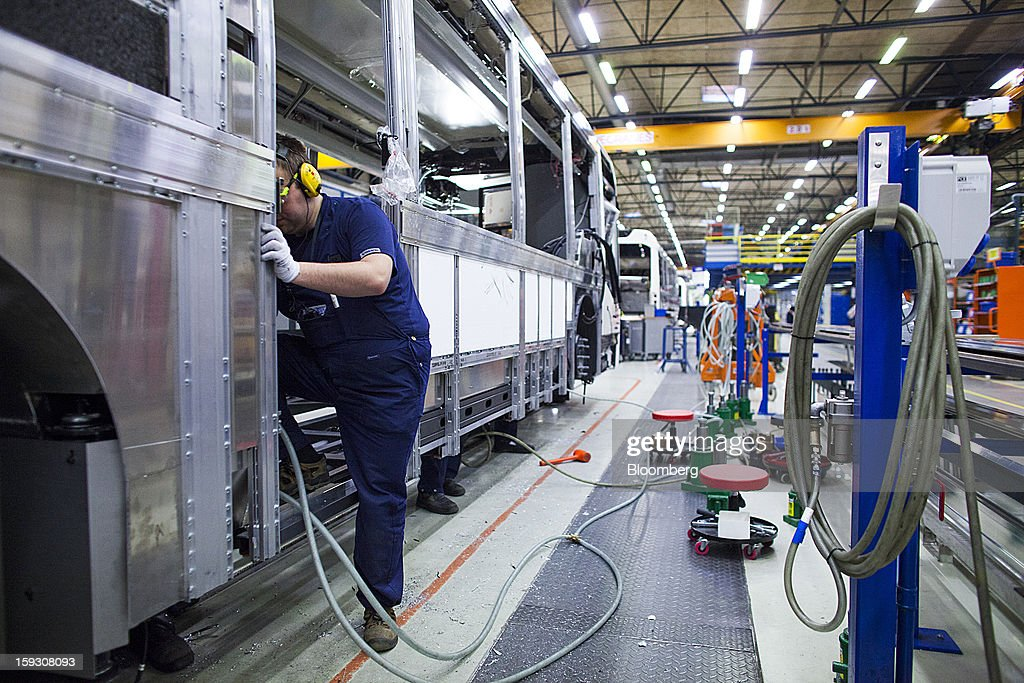 A worker stands in a doorway during the assembly of the upper structure of a bus at Volvo AB's bus manufacturing plant in Wroclaw, Poland, on Friday, Jan. 11, 2013. Volvo plans to end bus making in Saeffle by June 2013, and will consolidate the business in Europe to its main plant in Wroclaw, Poland, the Gothenburg, Sweden-based company said. Photographer: Bartek Sadowski/Bloomberg via Getty Images