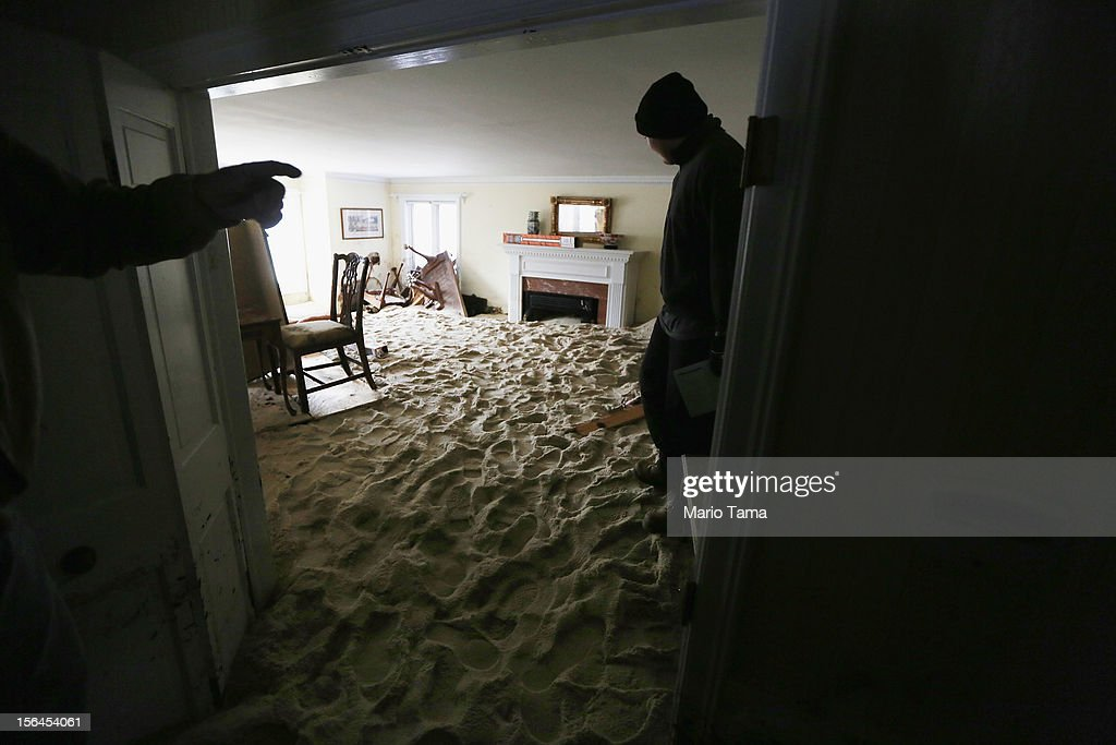 A worker stands in a living room filled with sand washed in by Superstorm Sandy on November 14, 2012 in Bay Head, New Jersey. Many residents of the hard hit seaside town remain without power following Superstorm Sandy.