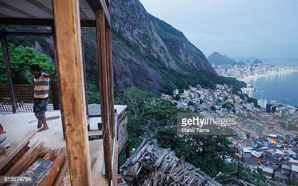 A worker stands in a partially completed construction project in the Vidigal 'favela' or community on March 3 2016 in Rio de Janeiro Brazil The...