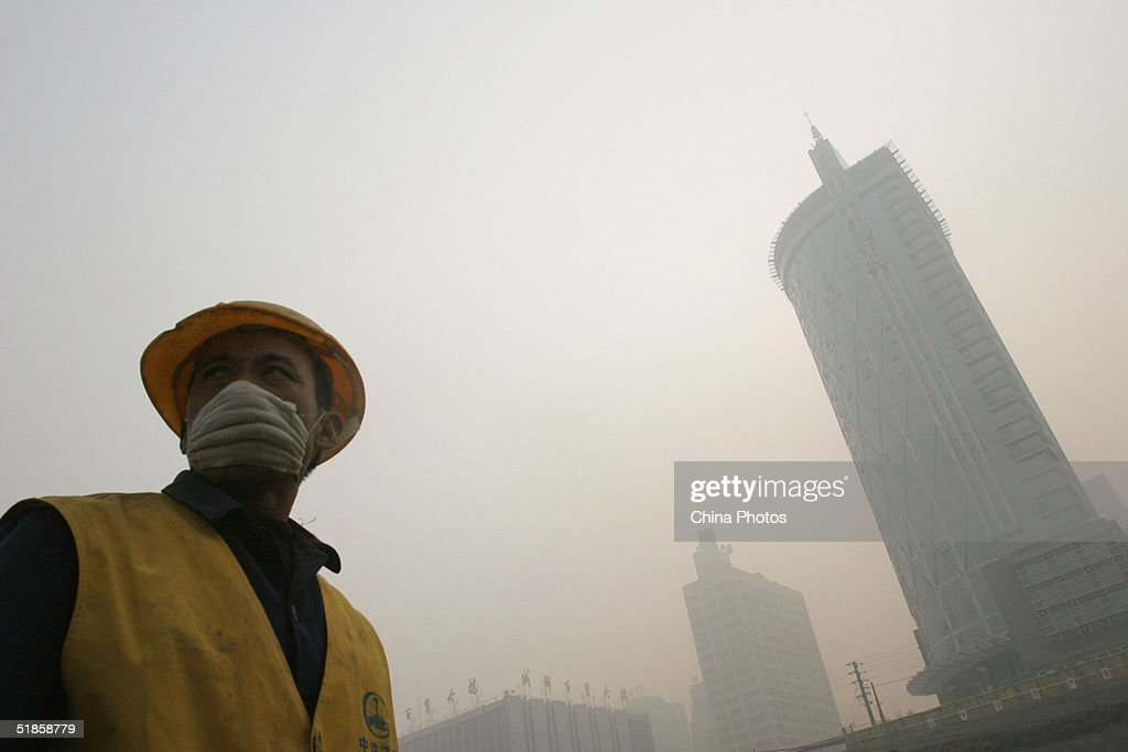 A worker stands in a street in heavy fog December 14, 2004 in Chengdu, Sichuan Province of China. The heaviest fog since winter has in some areas reduced visibility is to less than 10 meters (11 yards).