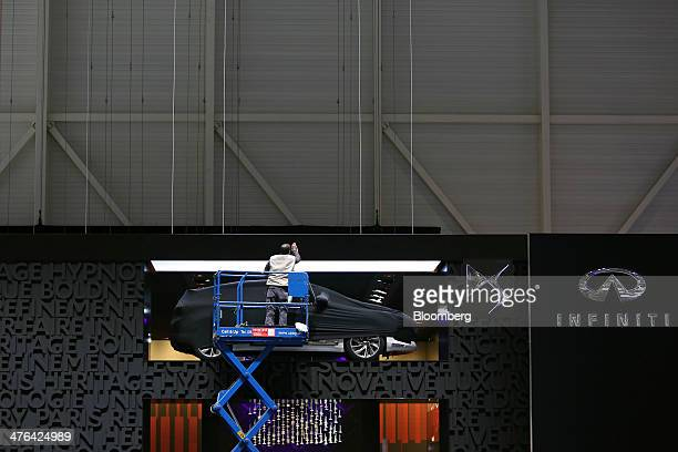 A worker stands in an extended scissor lift to clean the surface area alongside a wallmounted Infinty automobile produced by Nissan Motor Co ahead of...