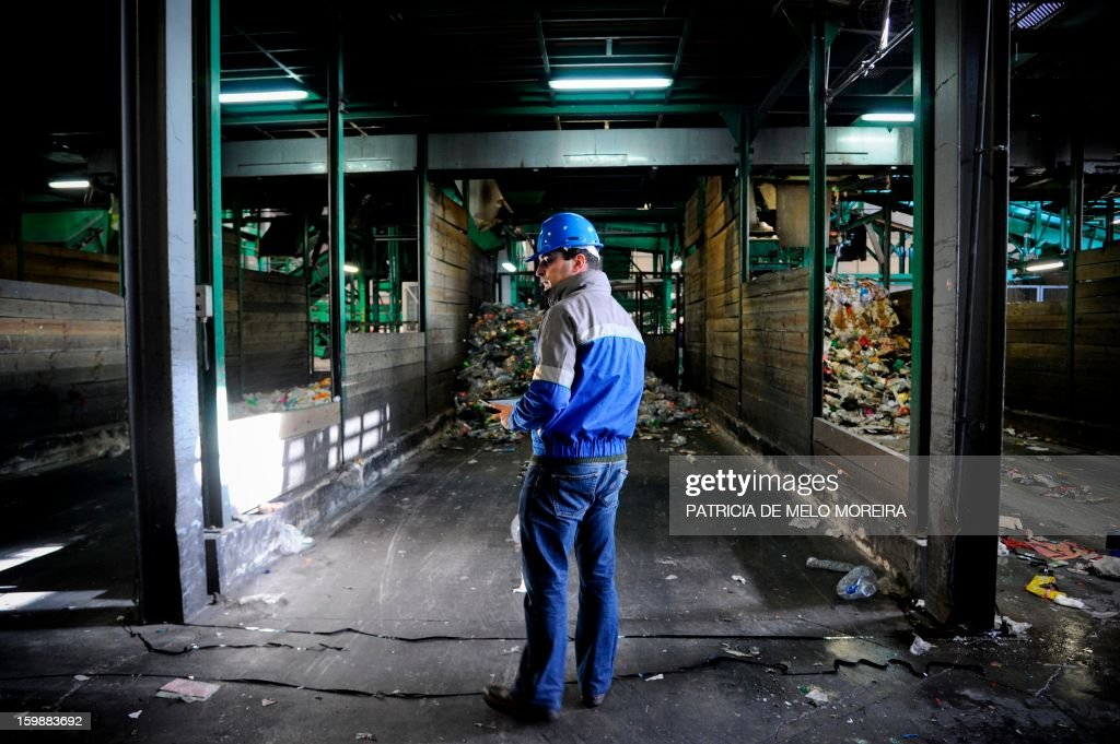 A worker stands in front a machine that separates garbage at Valorsul, a waste treatment plant, in Lisbon on January 22, 2013.