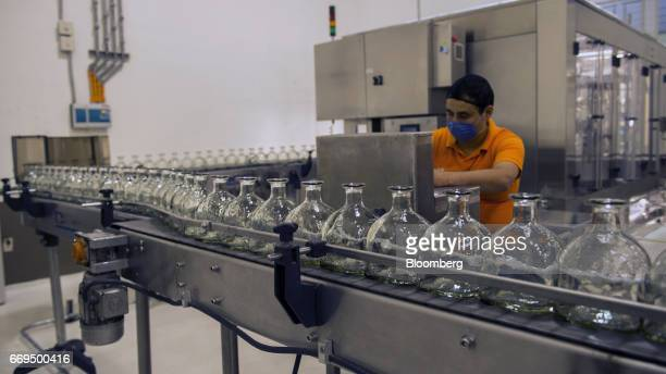 A worker stands in front of a control panel as empty tequila bottles move down a conveyor belt at the Patron Spirits Co distillery in Atotonilco El...
