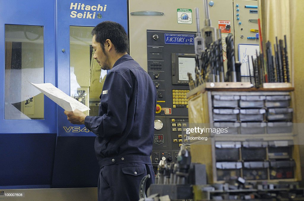 A worker stands in front of a machine for molding metals at a plant in the Ota Ward of Tokyo, Japan, on Thursday, May 20, 2010. Japan's economy grew less than forecast in the first quarter as an export-led recovery failed to stoke consumer spending, putting pressure on the central bank to do more to end deflation as it begins a two-day meeting. Photographer: Akio Kon/Bloomberg via Getty Images