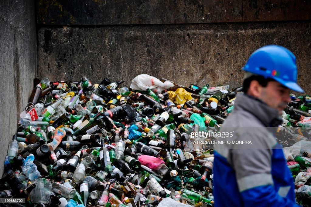 A worker stands in front of a pile of glass bottles for recycling at Valorsul, a waste treatment plant, in Lisbon on January 22, 2013.