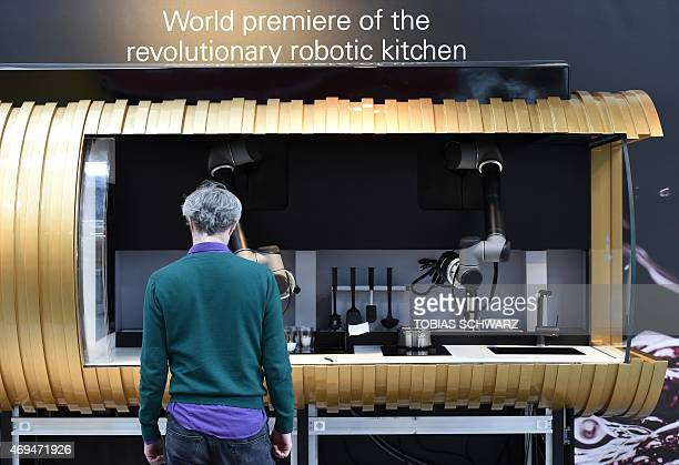 Worker stands in front of a robotic kitchen prior to the opening of the Hannover Messe industrial trade fair in Hanover central Germany on April 12...