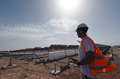 A worker stands in front of a solar array that is part of the Noor 1 solar power project in Ouarzazate on October 19 2014 Morocco's first solar...