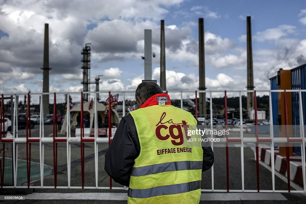 A worker stands in front of the Total oil refinery of Feyzin, near Lyon, central-eastern France, on May 24, 2016, during a strike at the plant to protest against government labour reforms. France's government stepped up efforts on May 24 to break blockades and strikes at refineries that are threatening to paralyse the country just three weeks ahead of the Euro 2016 football tournament. Six out of eight of the refineries in France have either stopped operating or have reduced output due to strikes and blockades. PACHOUD