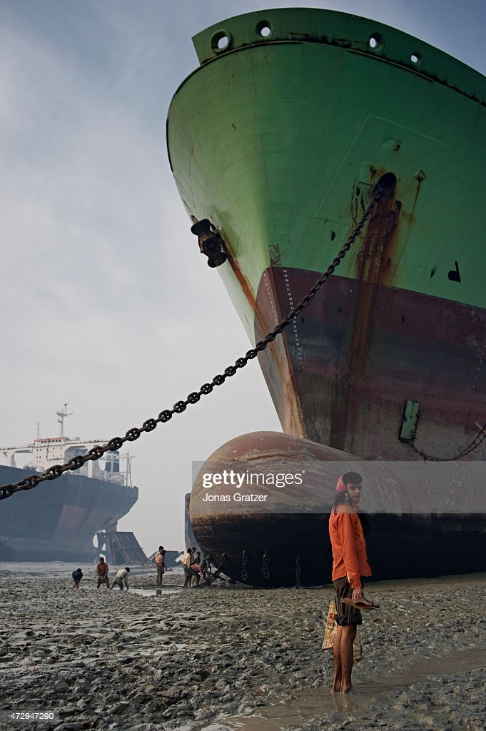 A worker stands in the muddy water in front of a mega freighter that has been parked on Chittagong beach to be disassembled Where do the mega...