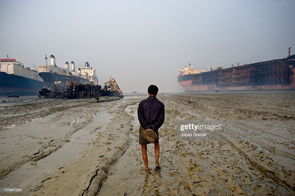 A worker stands in the muddy water in front of mega freighters that have been parked on Chittagong beach to be disassembled Where do the mega...