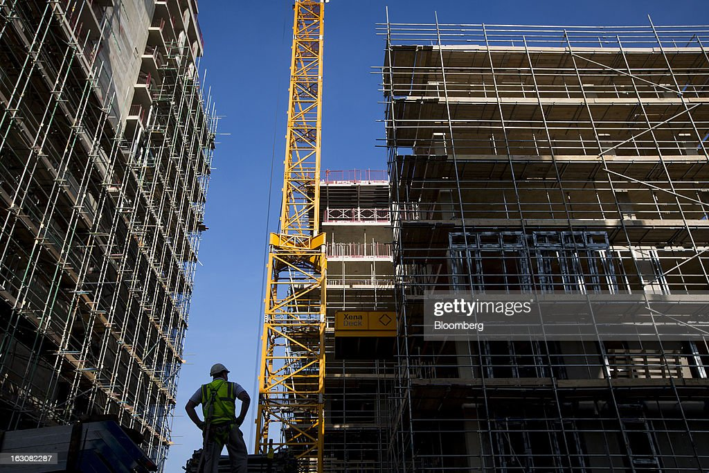 A worker stands near apartments under construction on the Radius development by Taylor Wimpey Plc in the Wandsworth district of London, U.K., on Monday, March 4, 2013. Central London luxury-home prices unexpectedly rose at the fastest pace in 10 months in February as the British pound's depreciation helped attract international investors, Knight Frank LLP said. Photographer: Jason Alden/Bloomberg via Getty Images
