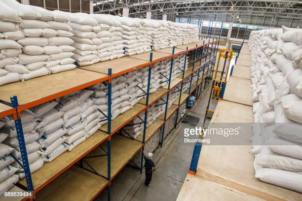 A worker stands near bags of processed garlic stacked in bags inside a warehouse at a Nithi Foods Co factory in the San Pa Tong district of Chiang...