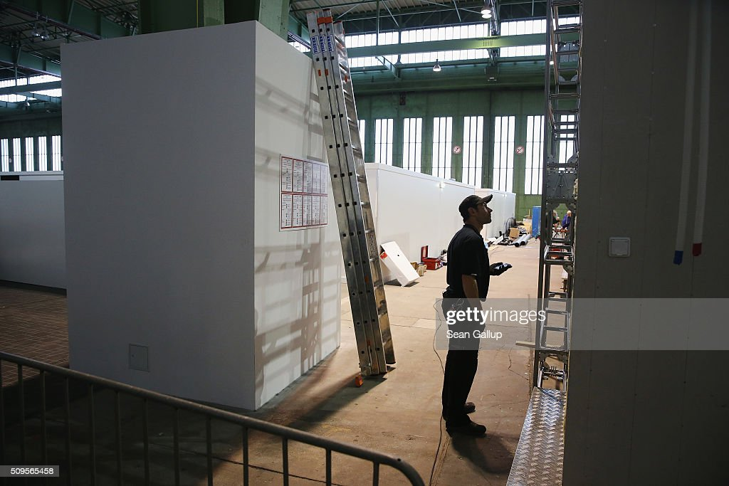 A worker stands near cubicles furnished with bunk beds ready to accommodate refugees and asylum applicants in Hangar 6 of former Tempelhof Airport on February 11, 2016 in Berlin, Germany. Tempelhof, once an airport in the city center and first built in the 1930s, now houses approximately 2,600 refugees in three former hangars. Berlin city authorities recently approved plans to expand its capacity to house the newcomers with an additional 90 shelters with space for 30,000 people. An estimated 50,000-80,000 migrants and refugees already live in Berlin. Germany received 1.1 million refugees and migrants in 2015 and is expecting to continue to receive large numbers in 2016.