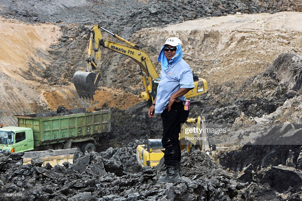 A worker stands near Komatsu Ltd. excavators and trucks at the PT Exploitasi Energi Indonesia open pit coal mine in Palaran, East Kalimantan province, Indonesia, on Friday, Sept. 13, 2013. Prices of power-station coal in Indonesia, the worlds biggest exporter, may be little changed in coming weeks, according to Bloomberg News survey. Photographer: Dadang Tri/Bloomberg via Getty Images