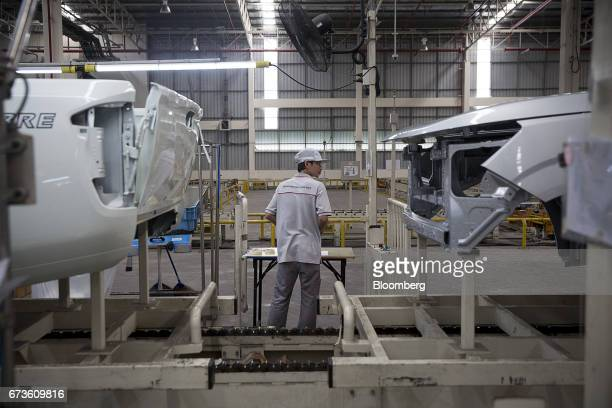 A worker stands near Nissan Motor Co Navara pickup truck bodies on an assembly line at the company's plant in Samut Prakan Thailand on Tuesday April...