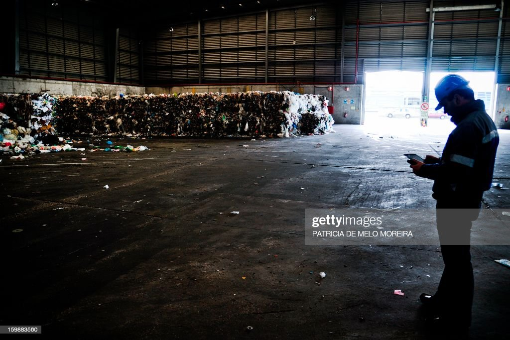 A worker stands near piles garbage for recycling at Valorsul, a waste treatment plant, in Lisbon on January 22, 2013.
