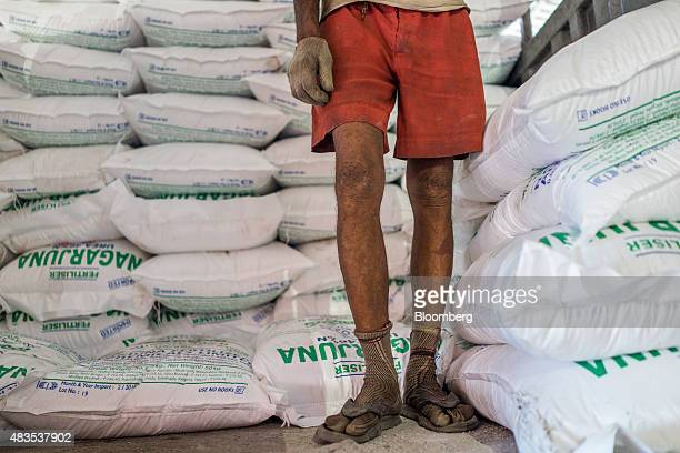 A worker stands next to bags of urea fertilizers inside a warehouse at the Kirshnapatnam Co port in Kirshnapatnam Andhra Pradesh India on Monday June...