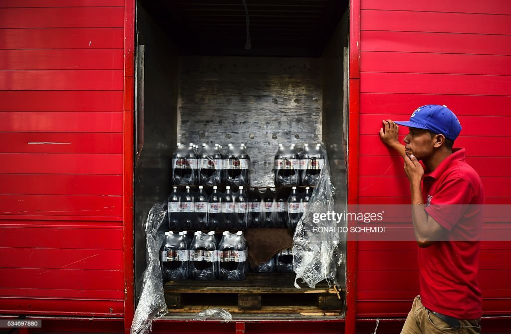 A worker stands next to bottles of Coca Cola that he is unloading from a truck in Caracas on May 27, 2016. Coca Cola suspended much of its distribution in Venezuela due to a shortage of sugar. / AFP / RONALDO