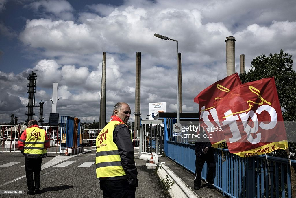 A worker stands next to French CGT union flags in front of the Total oil refinery of Feyzin, near Lyon, central-eastern France, on May 24, 2016, during a strike at the plant to protest against government labour reforms. France's government stepped up efforts on May 24 to break blockades and strikes at refineries that are threatening to paralyse the country just three weeks ahead of the Euro 2016 football tournament. Six out of eight of the refineries in France have either stopped operating or have reduced output due to strikes and blockades. PACHOUD