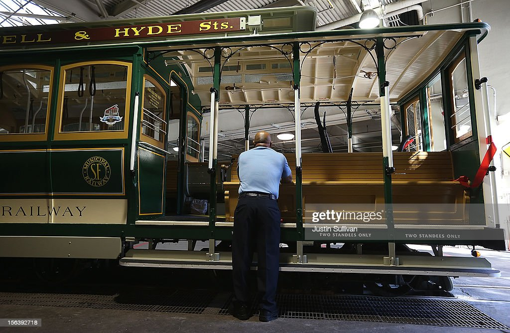 A worker stands next to San Francisco Cable Car #26 as he watches a service inauguration ceremony for the newly restored vintage Cable Car on November 14, 2012 in San Francisco, California. A service inauguration ceremony kicked off a new life for San Francisco Cable Car #26 that was originally built in 1890 and has been fully restored by hand and put back in service on the streets of San Francisco.