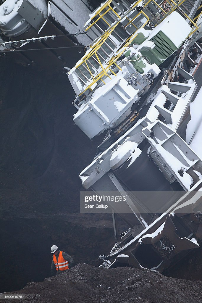 A worker stands next to the excavation wheel of a 950-tonne bucket excavator that had fallen over prior to attempting to set it upright following an accident at an open-pit coal mine on January 25, 2013 near Deutzen, Germany. The bucket excavator tipped over last summer after plateaus of clay and sand nearby gave way, pushing a layer of coal underneath. The excavator had been lying severely tilted to one side ever since at the Vereinigtes Schleenhain mine, which is operated by Mibrag. Open-pit lignite coal mines are still common across eastern Germany and produce coal for local electricity production.