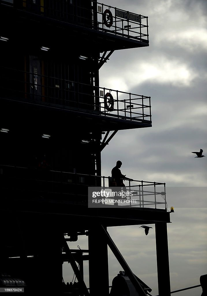 A worker stands on a balcony of a platform boat near the Costa Concordia cruise ship at the port the Italian island of Isola del Giglio, on January 12, 2013. A year on from the Costa Concordia tragedy in which 32 people lost their lives, the giant cruise ship still lies keeled over on an Italian island and its captain Francesco Schettino has become a global figure of mockery.