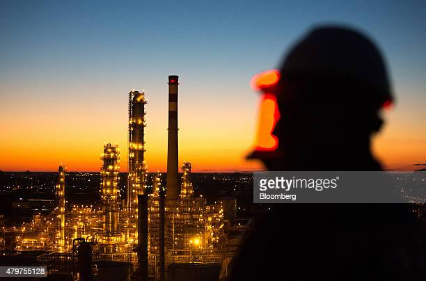 A worker stands on a high level platform and looks out across the illuminated Atyrau oil refinery operated by KazMunaiGas National Co in Atyrau...