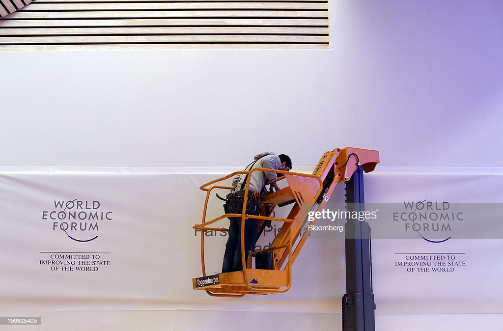 A worker stands on a hydraulic platform to secure a banner inside the Congress Centre ahead of The World Economic Forum meeting (WEF) meeting in Davos, Switzerland, on Monday, Jan. 21, 2013. This week the business elite gathers in the Swiss Alps for the 43rd annual meeting of the World Economic Forum in Davos, the five day event runs from Jan. 23-27. Photographer: Simon Dawson/Bloomberg via Getty Images
