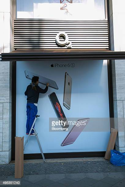 A worker stands on a ladder before removing an Apple Inc iPhone 6 smartphone advertisement from the window of an O2 mobile phone store operated by...